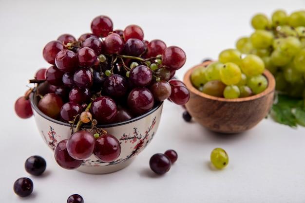 Vista lateral de uvas vermelhas e bagas de uvas brancas em tigelas com uvas de uvas brancas e folhas no fundo branco