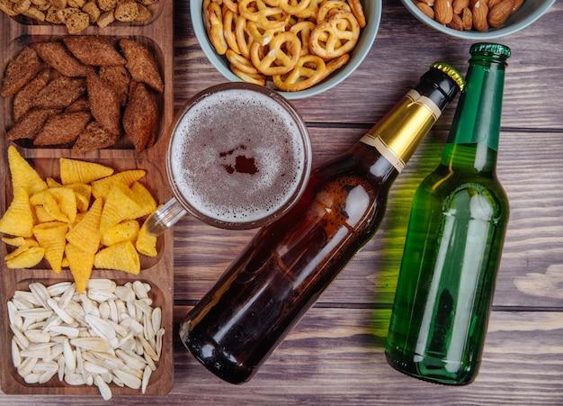 Vista lateral de variados petiscos de cerveja sementes de girassol pão biscoitos e mini pretzels com cerveja no rústico