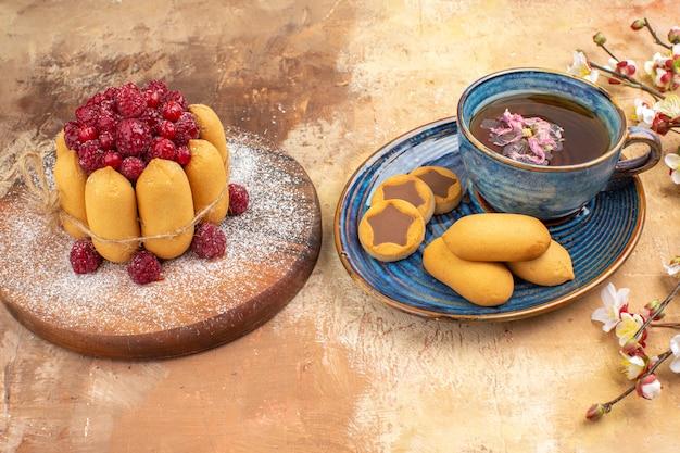 Vista lateral de vários biscoitos e bolo macio, uma xícara de chá e barras de chocolate de flores