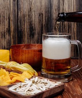 Vista lateral de vários lanches de cerveja salgada em uma bandeja de madeira e derramar cerveja em uma caneca em madeira rústica