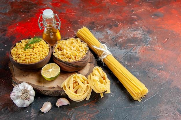 Vista lateral de vários tipos de massas não cozidas e garrafa de óleo de limão e alho em fundo de cor mista