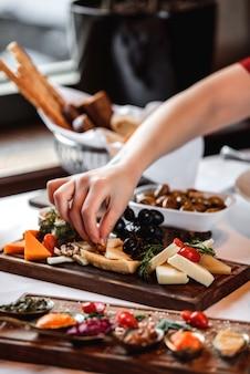 Vista lateral de vários tipos de queijo com uvas nozes e mel na bandeja de madeira
