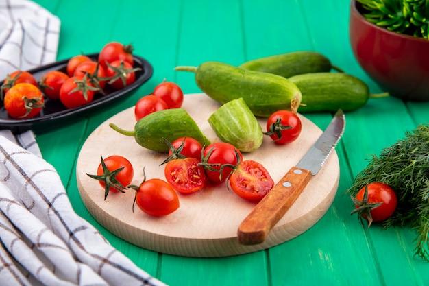 Vista lateral de vegetais como pepino e tomate com faca na tábua e monte de endro e pano xadrez em verde