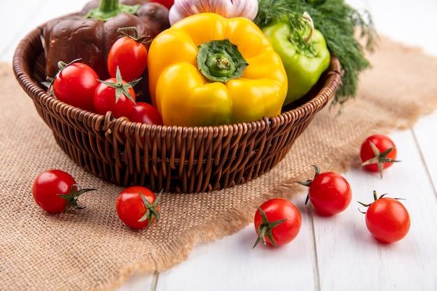 Vista lateral de vegetais como pimenta, alho, tomate, endro na cesta e no saco de madeira