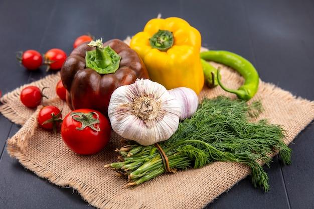 Vista lateral de vegetais como pimenta, alho, tomate, endro, saco, preto
