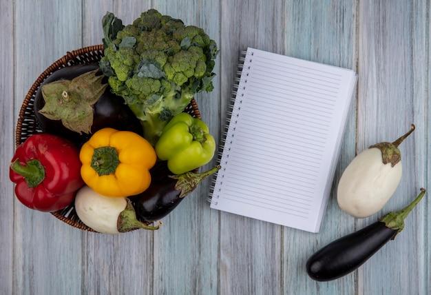 Vista lateral de vegetais como pimenta brócolis e berinjela em uma cesta com bloco de notas no fundo de madeira com espaço de cópia