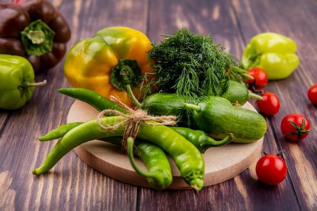 Vista lateral de vegetais como pimenta pepino endro na tábua com tomates na madeira