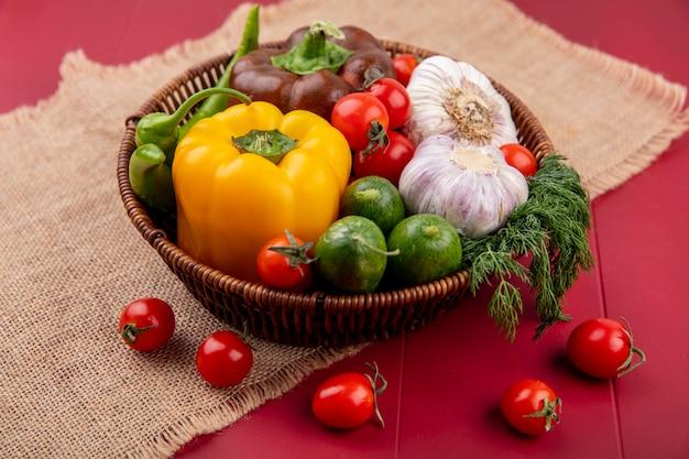 Vista lateral de vegetais como pimenta pepino tomate alho endro na cesta no saco e vermelho