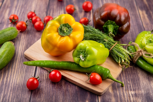 Vista lateral de vegetais como pimentão e endro na tábua de cortar com pepino, tomate e faca na madeira