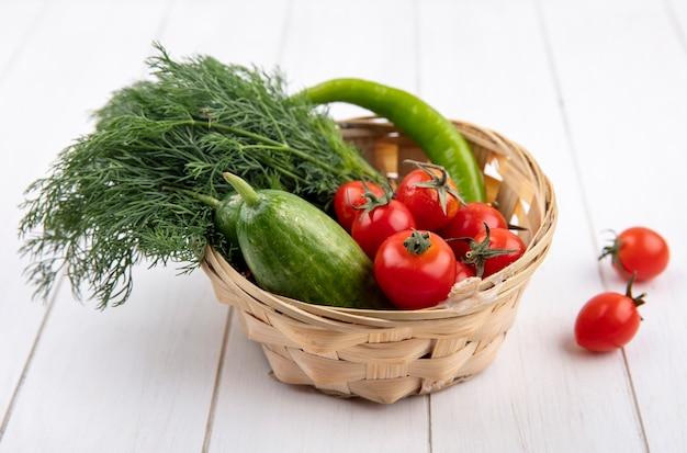 Vista lateral de vegetais como tomate endro pepino em uma cesta na madeira
