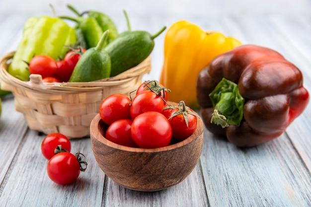 Vista lateral de vegetais como tomate pimenta pepino em uma tigela e na madeira