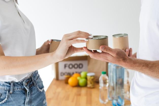 Vista lateral de voluntários trocando latas por caixas de doação de alimentos
