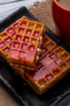 Vista lateral de waffles com calda de morango em uma bandeja preta e uma xícara de cacau