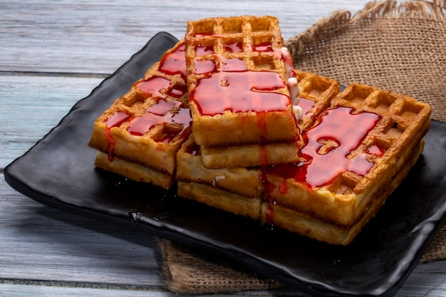 Vista lateral de waffles com calda de morango em uma bandeja preta