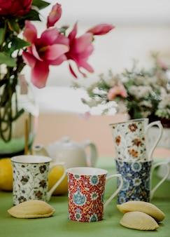 Vista lateral de xícaras de chá com padrão oriental e doçura tradicional do azerbaijão shekerbura na parede floral