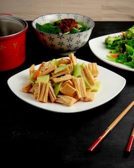Vista lateral de yuba e pepino com molho em um prato