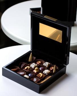 Vista lateral decorado doces de chocolate em uma caixa de ouro preto