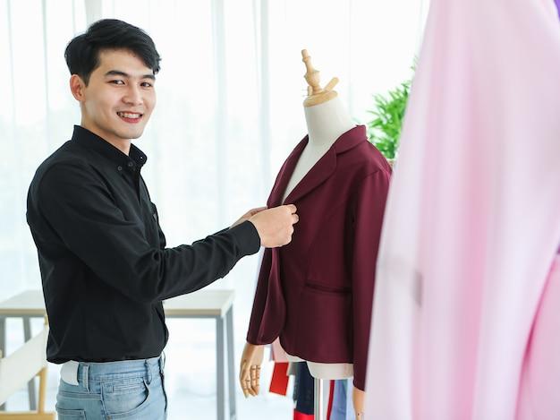 Vista lateral do alegre designer masculino asiático, colocando uma jaqueta elegante no manequim enquanto trabalhava.