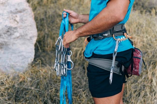 Vista lateral do alpinista com corda