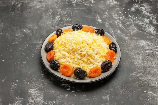 Vista lateral do arroz em close-up, arroz e as apetitosas frutas secas na mesa