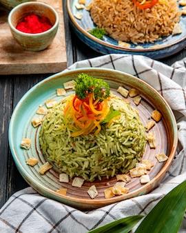 Vista lateral do arroz japonês com legumes em um prato na superfície de madeira