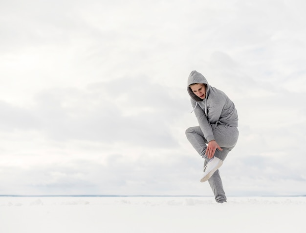 Vista lateral do artista de hip hop dançando na neve com espaço de cópia