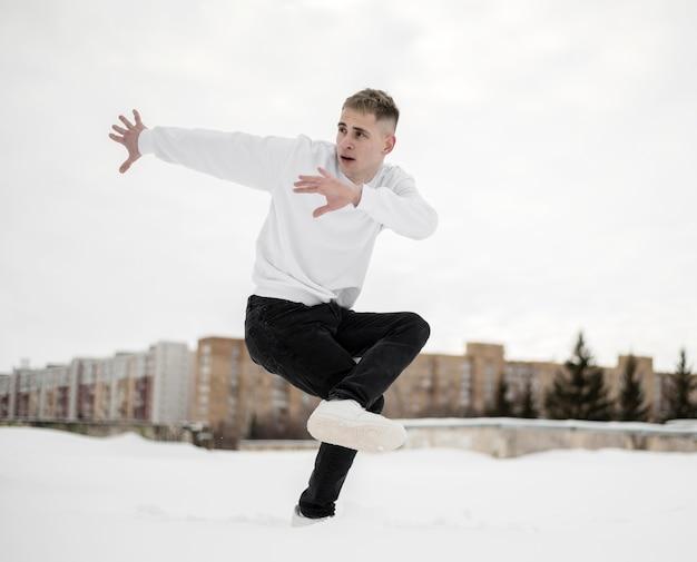 Vista lateral do artista de hip-hop posando enquanto dança