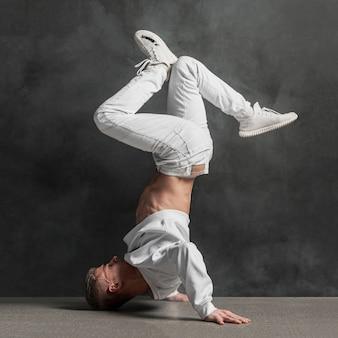 Vista lateral do artista masculino em jeans e tênis segurando as pernas