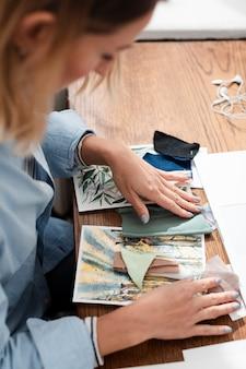 Vista lateral do artista trabalhando na mesa
