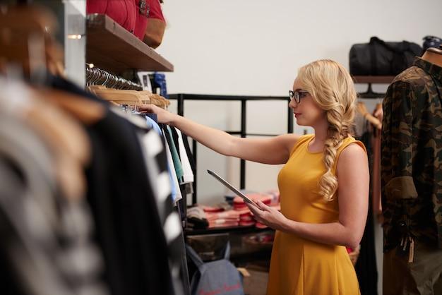 Vista lateral do assistente de loja feminino, verificando a mercadoria na loja de roupas