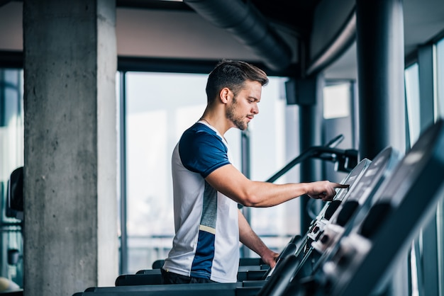 Vista lateral do atleta, ajustando a velocidade na esteira, fazendo exercícios aeróbicos no ginásio.