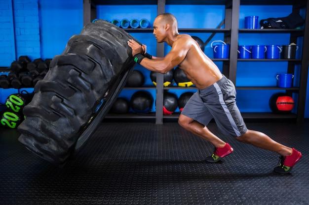 Vista lateral do atleta do sexo masculino empurrando o pneu