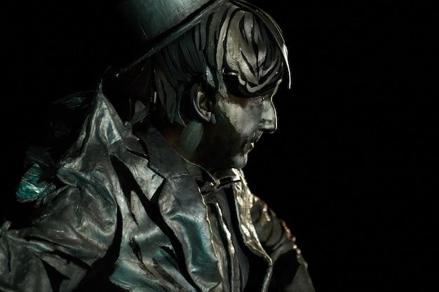 Vista lateral do ator mímico com maquiagem facial, vestindo um cilindro e um terno pintado que parece uma estátua em fundo preto. arte performática teatral e pantomima