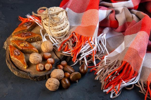 Vista lateral do baklava tradicional do azerbaijão com nozes inteiras e pães de arroz na manta com borla
