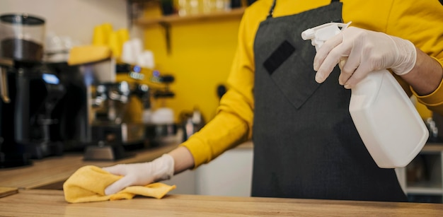 Vista lateral do barista com luvas de látex, mesa de limpeza