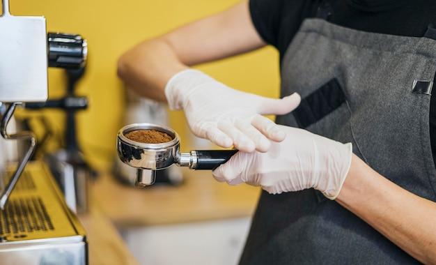 Vista lateral do barista com luvas de látex, preparando o café para a máquina