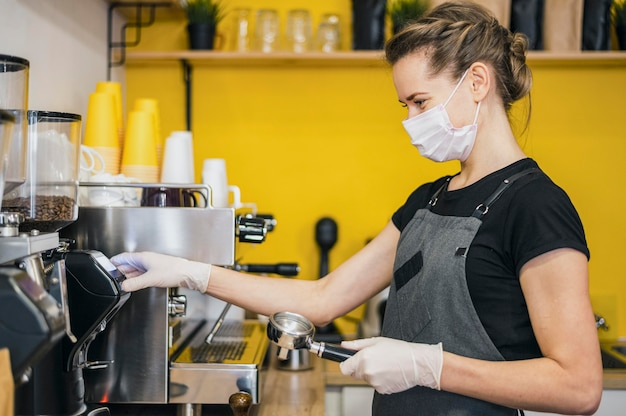 Vista lateral do barista feminino com luvas de látex, preparando o café para a máquina
