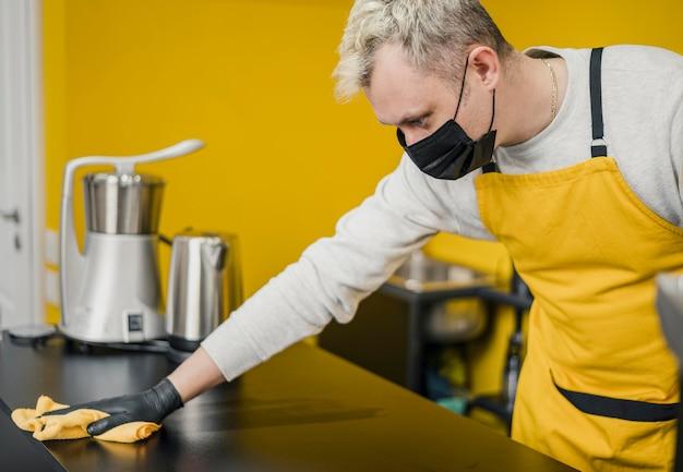 Vista lateral do barista masculino com máscara médica, limpando a superfície da mesa