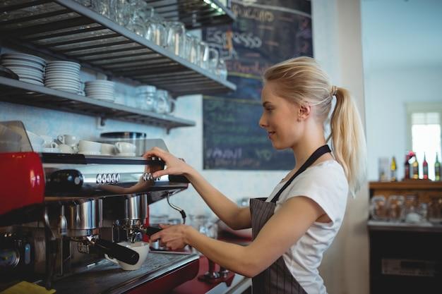 Vista lateral do barista usando a máquina de café expresso na casa de café