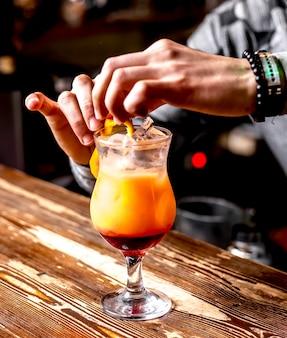 Vista lateral do barman faz um cocktail de decoração de casca de laranja