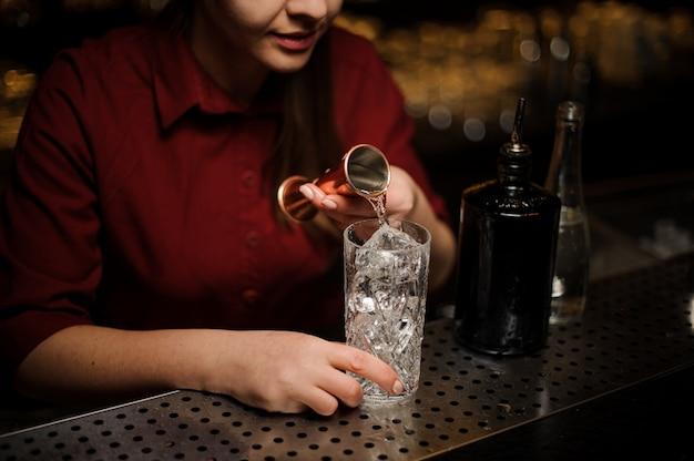 Vista lateral do barman feminino derramando um pouco de gin em um copo de coquetel