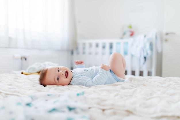 Vista lateral do bebê gordinho adorável seis meses de idade, deitado na cama, sorrindo e olhando para a câmera.