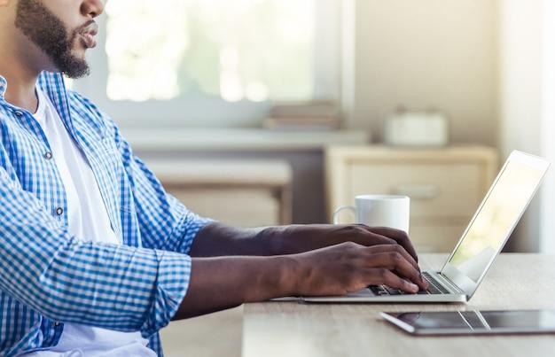 Vista lateral do belo homem afro-americano está usando um laptop.
