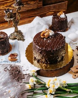 Vista lateral do bolo coberto com chocolate e nozes em cima da mesa