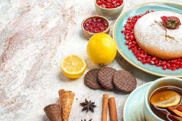 Vista lateral do bolo com morangos, o bolo, uma xícara de chá ao lado das bagas de anis estrelado