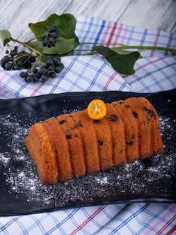 Vista lateral do bolo com passas, decorado com fatia de kumquat e açúcar em pó em uma placa preta