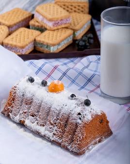 Vista lateral do bolo com passas e açúcar em pó e um copo de leite na toalha da mesa