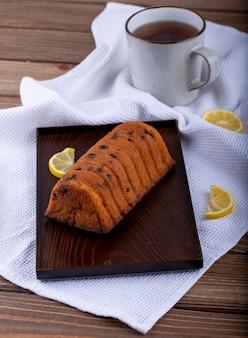 Vista lateral do bolo com passas e fatias de limão em uma placa de madeira e uma caneca de chá na toalha da mesa