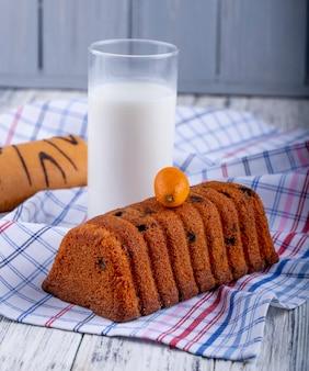 Vista lateral do bolo com passas e um copo de leite numa toalha de mesa
