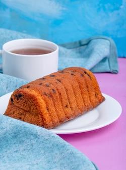 Vista lateral do bolo com passas em um prato branco e uma xícara de chá em fundo azul e roxo